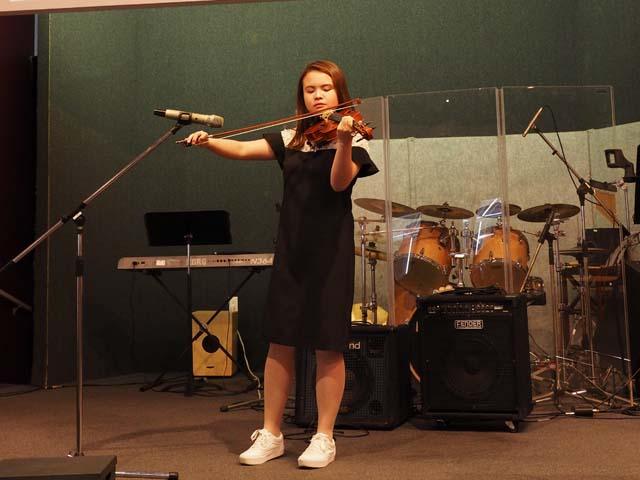 girl playing violin at school talent show